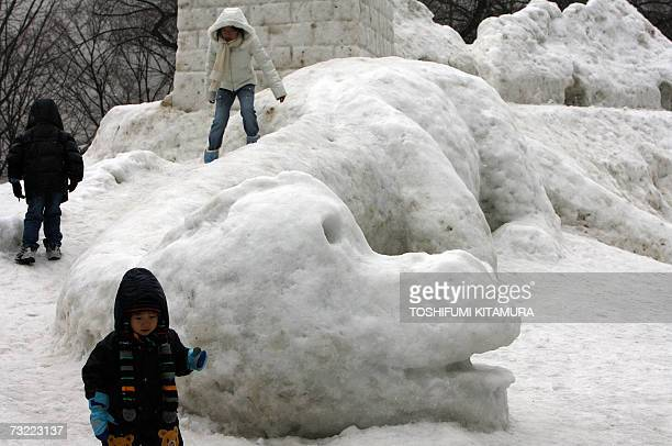 Children play around a snow sculpture of a dinosaur at the Odori park in central Sapporo 06 February 2007 The annual Sapporo Snow Festival started...