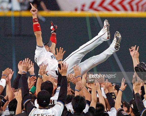 Former New York Mets outfielder Tsuyoshi Shinjo of the Pacific League champion Nippon Ham Fighters is tossed up in the air by his teammates as he...