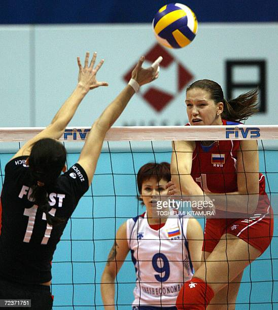 Maria Borodakova of Russia spikes a ball past a block by German Christiane Furst as Russia's Svetlana Kryuchkova looks on during their Pool B match...