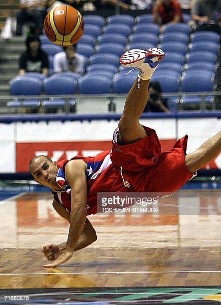 Puerto Rican Carlos Arroyo dives to pass the ball during the Group D preliminary round in the World Basketball Championship against Senegal in...