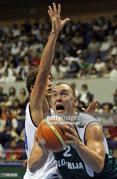 Slovenia's Marko Milic takes a look at the basket after passing Italy's Marco Belinelli during their Group D preliminary round match on the second...