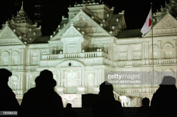 Visitors look at a 4/5 scale snow sculpture of Bangkok's Chakri Maha Prasat Grand Palace at the Odori park in central Sapporo 05 February 2007 The...