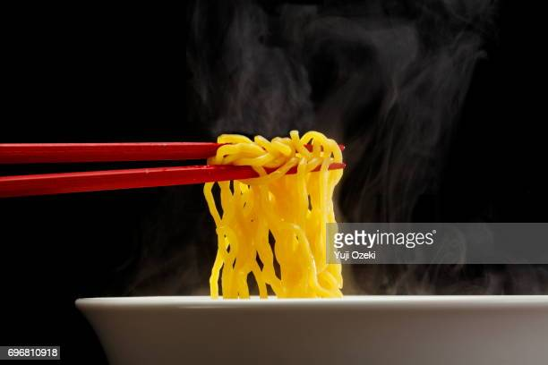 Sapporo ramen noodle lifted up by red chopsticks with steam against black background