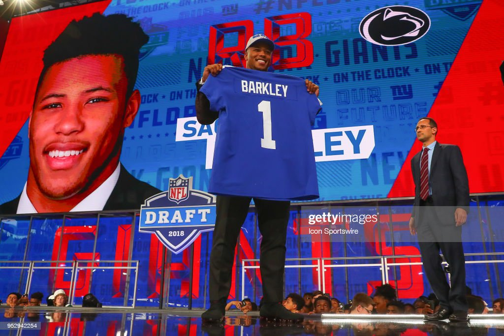 Saquon Barkley holds up a New York Giants Jersey after being selected by the New York Giants with the 2nd pick during the First Round of the 2018 NFL Draft on April 26, 2018 at AT&T Stadium in Arlington Texas.