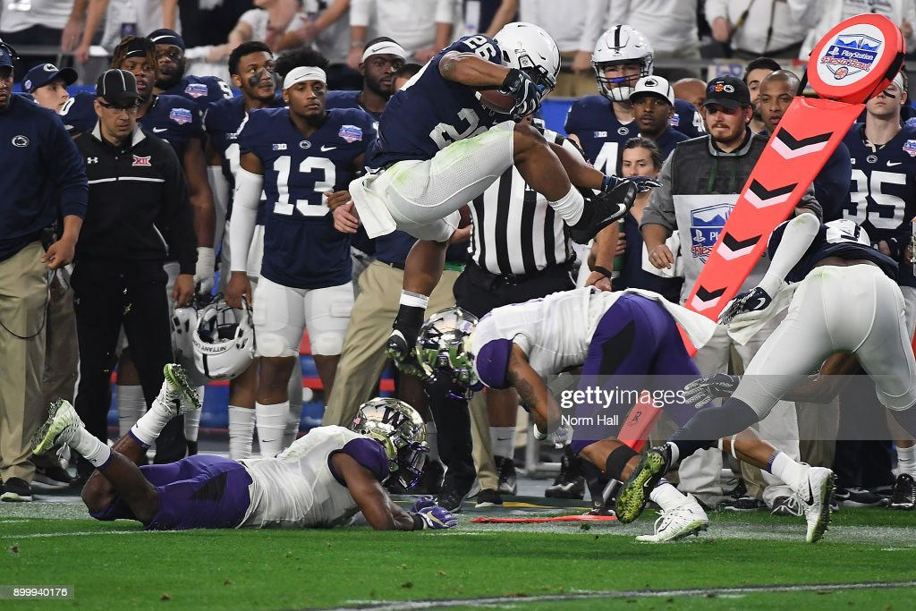 Saquon Barkley #26 of Penn State Nittany Lions leaps over defenders Austin Joyner #4 and Keishawn Bierria #7 of the Washington Huskies during the second quarter of the Playstation Fiesta Bowl at University of Phoenix Stadium on December 30, 2017 in Glendale, Arizona. Penn State won 35-28.