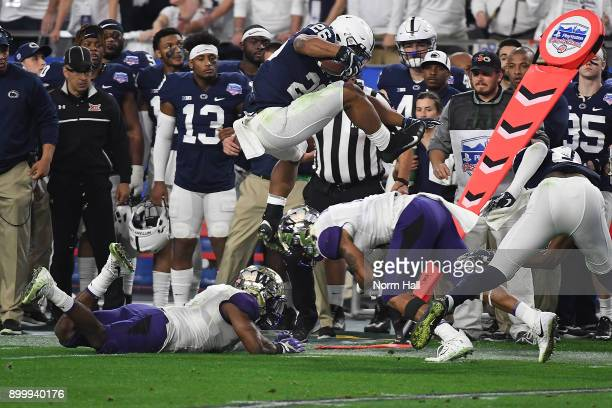 Saquon Barkley of Penn State Nittany Lions leaps over defenders Austin Joyner and Keishawn Bierria of the Washington Huskies during the second...