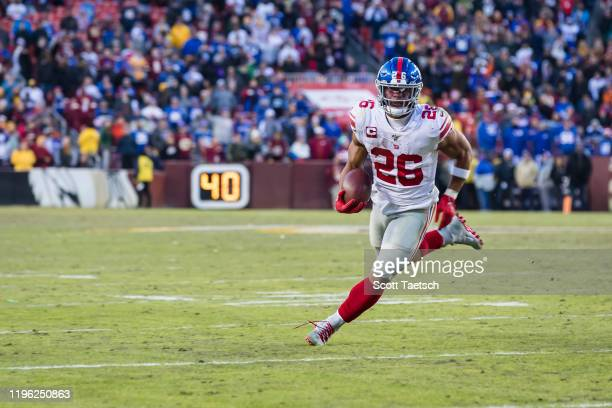 Saquon Barkley of the New York Giants carries the ball against the Washington Redskins defends during overtime at FedExField on December 22, 2019 in...