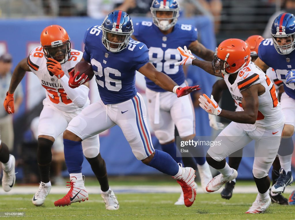 Saquon Barkley #26 of the New York Giants carries the ball as Damarious Randall #23 of the Cleveland Browns defends in the first quarter during their preseason game on August 9,2018 at MetLife Stadium in East Rutherford, New Jersey.