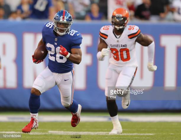 Saquon Barkley of the New York Giants carries the ball as Emmanuel Ogbah of the Cleveland Browns in the first quarter during their preseason game on...