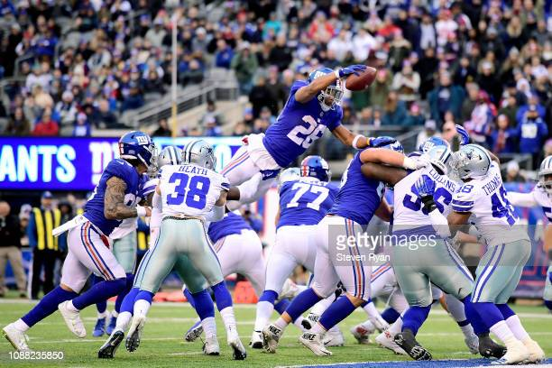 Saquon Barkley of the New York Giants dives across the goalline for a fourth quarter touchdown against the Dallas Cowboys at MetLife Stadium on...