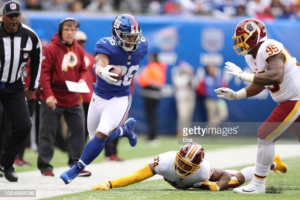 Saquon Barkley of the New York Giants extends in an attempt to reach the first down against Josh Norman and Da'Ron Payne of the Washington Redskins...