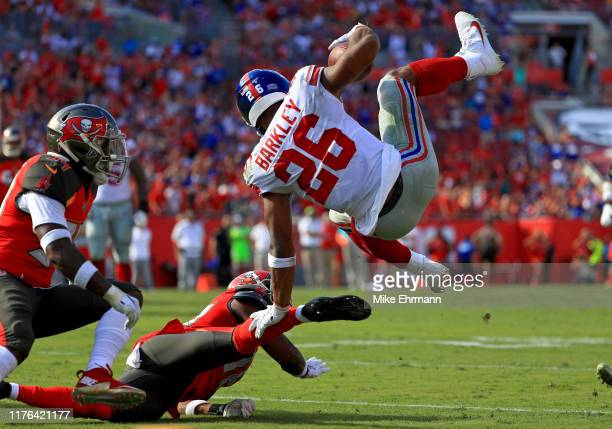 Saquon Barkley of the New York Giants gets up ended by M.J. Stewart of the Tampa Bay Buccaneers during a game at Raymond James Stadium on September...