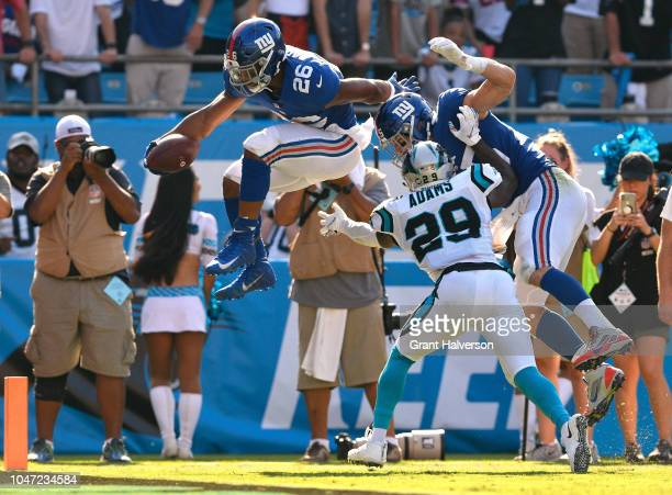 Saquon Barkley of the New York Giants hurdles over Mike Adams of the Carolina Panthers and into the end zone for a touchdown during their game at...