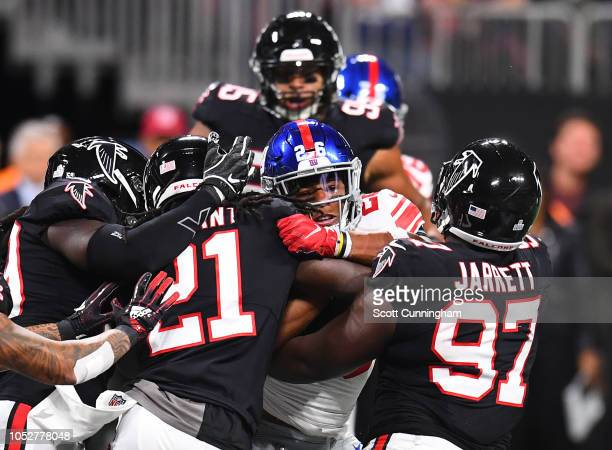 Saquon Barkley of the New York Giants is tackled by DeVondre Campbell Desmond Trufant and Grady Jarrett of the Atlanta Falcons in the second quarter...