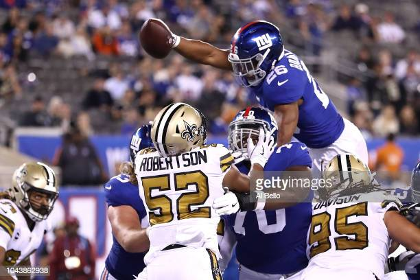Saquon Barkley of the New York Giants leaps for the end zone to score a touchdown against the New Orleans Saints during the fourth quarter at MetLife...