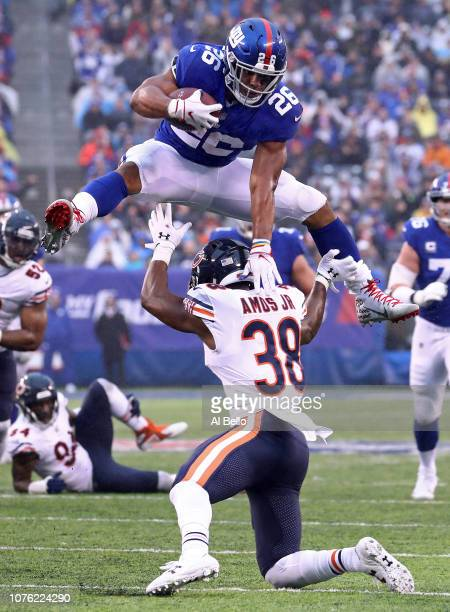 Saquon Barkley of the New York Giants leaps over Adrian Amos of the Chicago Bears for extra yardage during the third quarter at MetLife Stadium on...