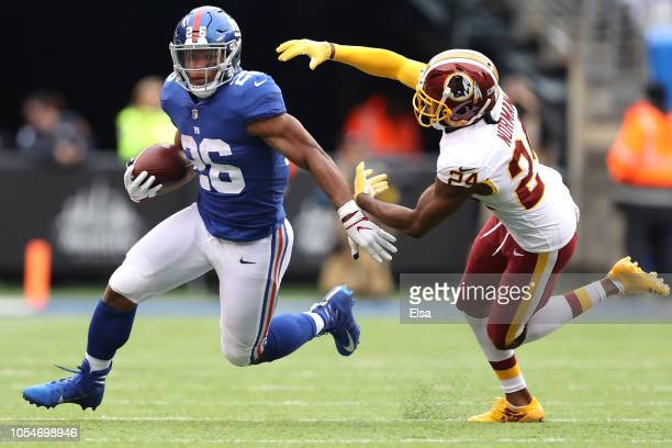 Saquon Barkley of the New York Giants makes a run against Josh Norman of the Washington Redskins at MetLife Stadium on October 28 2018 in East...