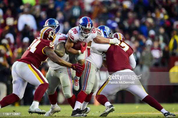 Saquon Barkley of the New York Giants rushes with the ball in overtime against the Washington Redskins at FedExField on December 22, 2019 in...