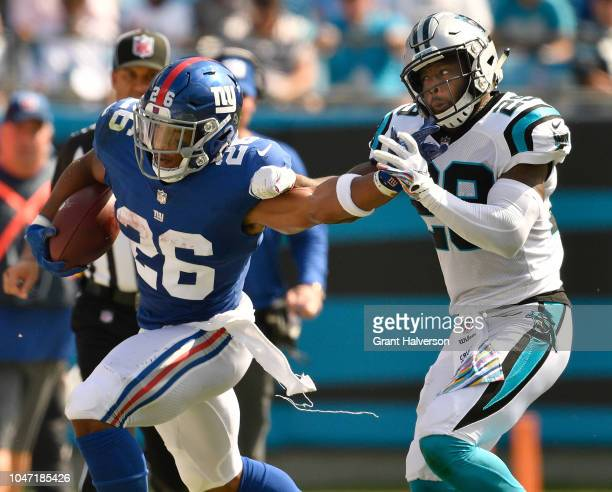 Saquon Barkley of the New York Giants stiffarms Mike Adams of the Carolina Panthers during their game at Bank of America Stadium on October 7 2018 in...