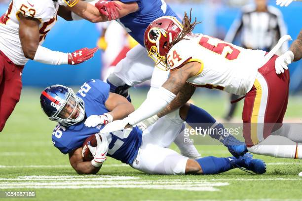 Saquon Barkley of the New York Giants takes a hit from Mason Foster of the Washington Redskins during the first quarter at MetLife Stadium on October...