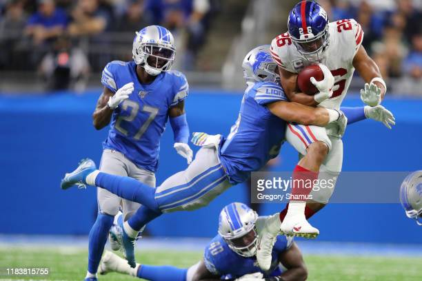 Saquon Barkley of the New York Giants tries to run through the tackle of Miles Killebrew of the Detroit Lions during a second half run at Ford Field...