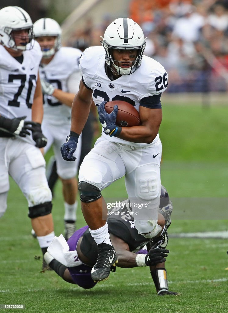 Saquon Barkley #26 of the Penn State Nittany Lions breaks a tackle attempt by Montre Hartage #24 of the Northwestern Wildcats on a 53 yard touchdown run at Ryan Field on October 7, 2017 in Evanston, Illinois. Penn State defeated Northwestern 31-7.