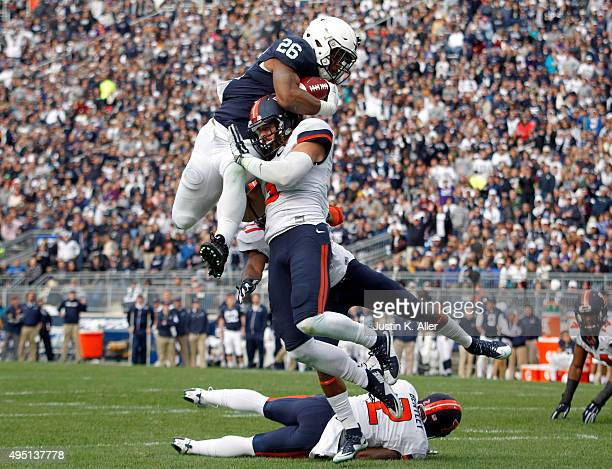 Saquon Barkley of the Penn State Nittany Lions jumps over defenders V'Angelo Bentley Taylor Barton and Eaton Spence of the Illinois Fighting Illini...