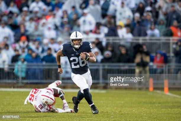 Saquon Barkley of the Penn State Nittany Lions slips by Kieron Williams of the Nebraska Cornhuskers during a touchdown run during the first quarter...