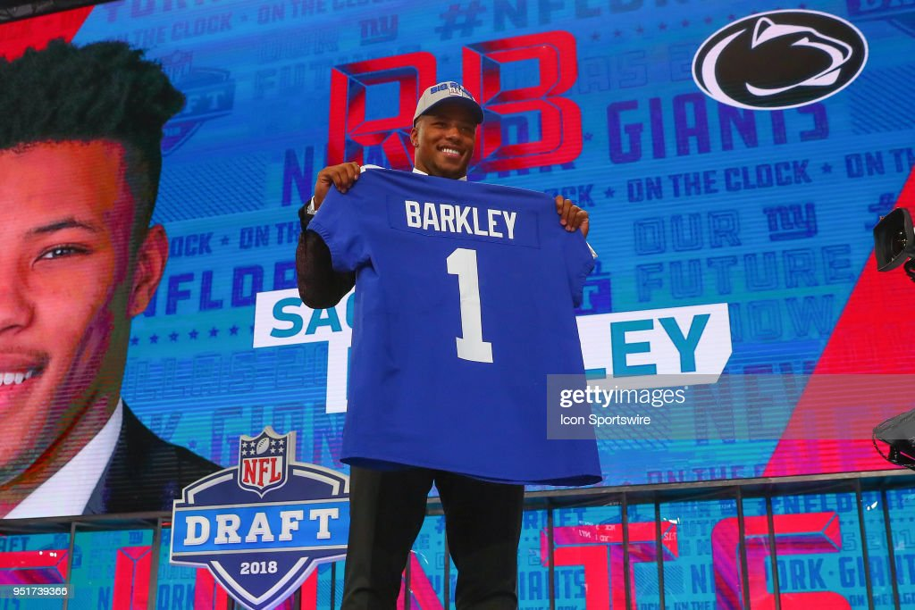Saquon Barkley poses for photos and holds a New York Giants Jersey as the second overall pick by the New York Giants in the first round at the 2018 NFL Draft at AT&T Statium on April 26, 2018 at AT&T Stadium in Arlington Texas.