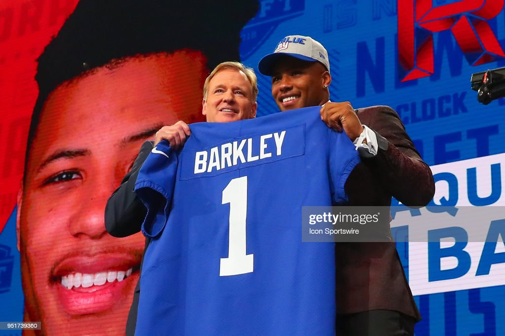 Saquon Barkley poses for photos with NFL Comissioner Roger Goodell and holds a New York Giants Jersey as the second overall pick by the New York Giants in the first round at the 2018 NFL Draft at AT&T Statium on April 26, 2018 at AT&T Stadium in Arlington Texas.