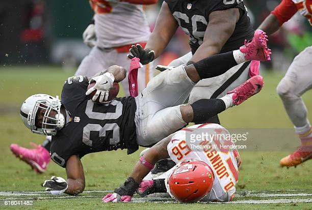 SaQwan Edwards of the Oakland Raiders returning a kickoff gets tackled by Derrick Johnson of the Kansas City Chiefs during an NFL football game at...