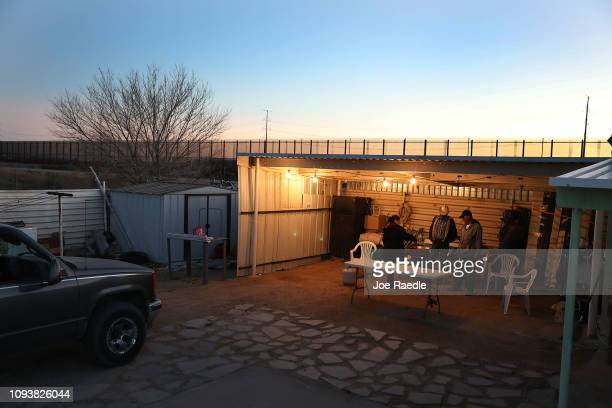 Sara Aguilar Renaldo Aguilar and Aaron Arreola cook dinner together outside their home which is near the US Border fence seen in the background on...