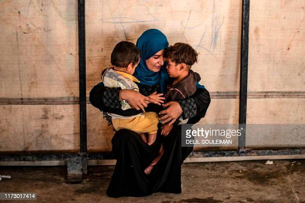 Sara al-Abdullah, a volunteer caring for 24 orphaned children reportedly linked with foreign fighters of the Islamic State group, holds two of them...