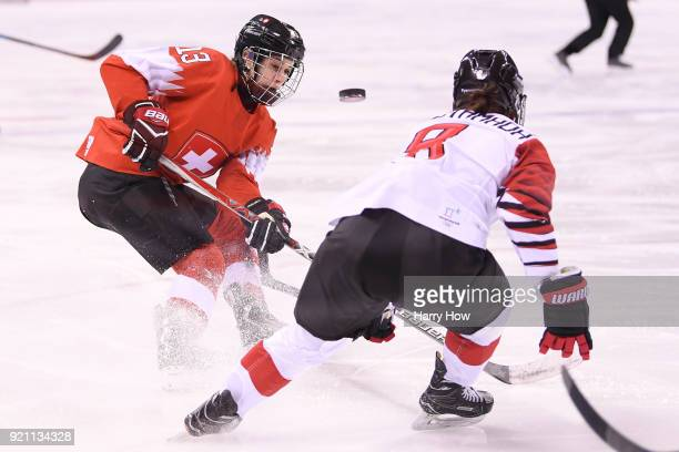 Sara Benz of Switzerland and Akane Hosoyamada of Japan compete for the puck in the first period during the Women's Ice Hockey Classification game on...