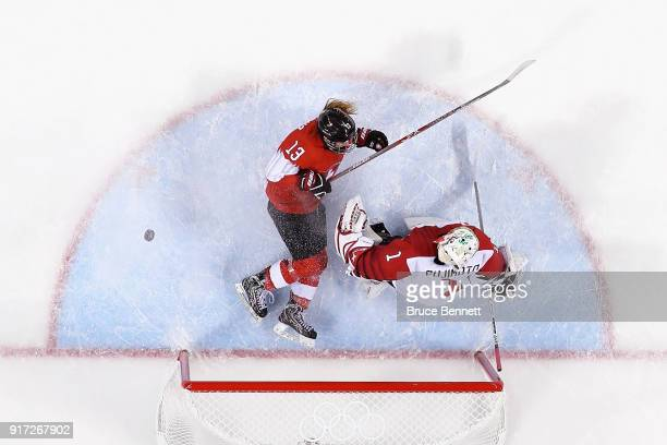 Sara Benz of Switzerland slides on the ice after scoring a goal against Nana Fujimoto of Japan in the second period during the Women's Ice Hockey...
