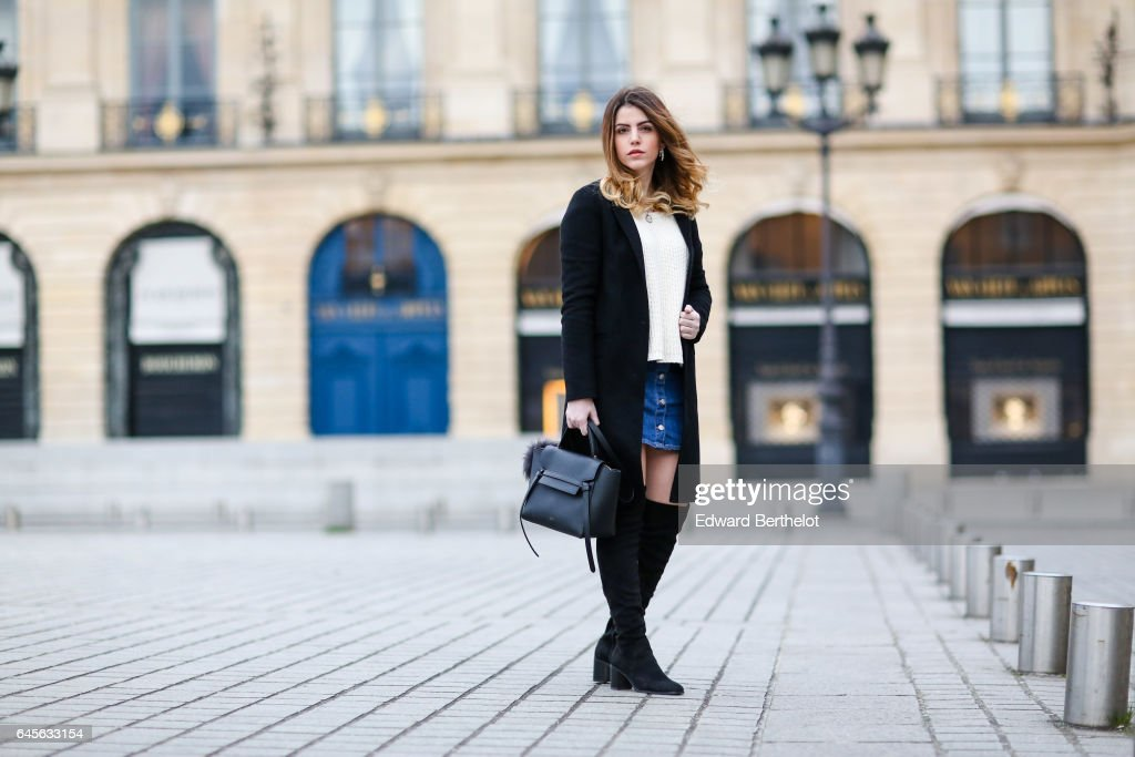 Sara Carnicella, fashion blogger from La Fille Rebelle, wears a Zara black coat, a Zara white pull over, Zara black thigh high boots, an H&M blue denim skirt, and a black Celine bag with a pompom, at Place Vendome, on February 26, 2017 in Paris, France.