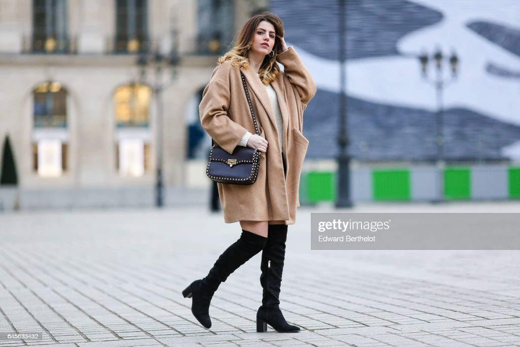 Sara Carnicella, fashion blogger from La Fille Rebelle, wears a Zara beige coat, a Zara white pull over, a Zara black skirt, Zara black thigh high boots, and a Valentino bag, at Place Vendome, on February 26, 2017 in Paris, France.