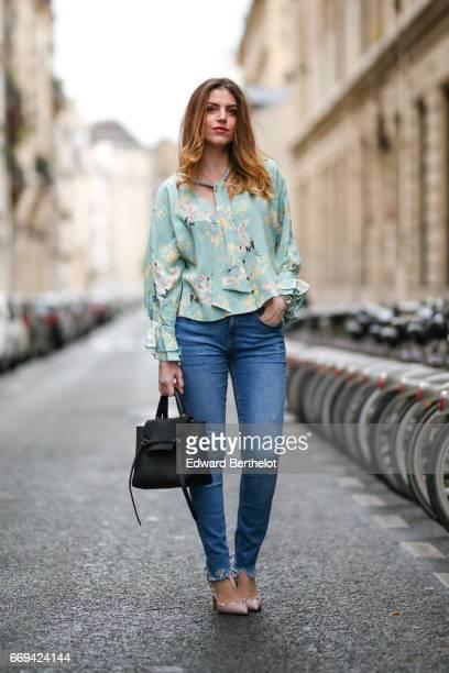 Sara Carnicella, fashion blogger La Fille Rebelle, wears Valentino shoes, a Celine black bag, a Zara green floral print top, and Zara blue denim...