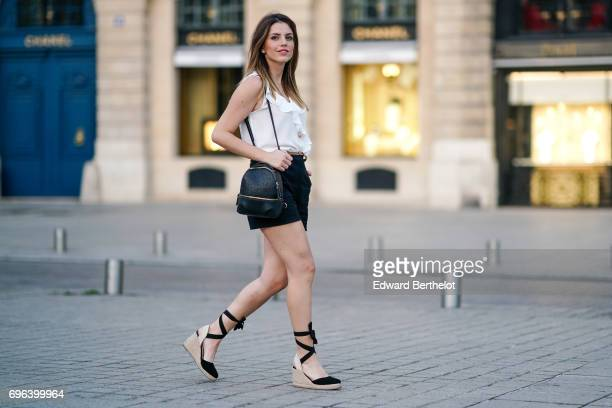 Sara Carnicella fashion blogger wears a Zara black leather bag a Zara white sleeveless top a Zara short and espadrille shoes at Place Vendome on June...