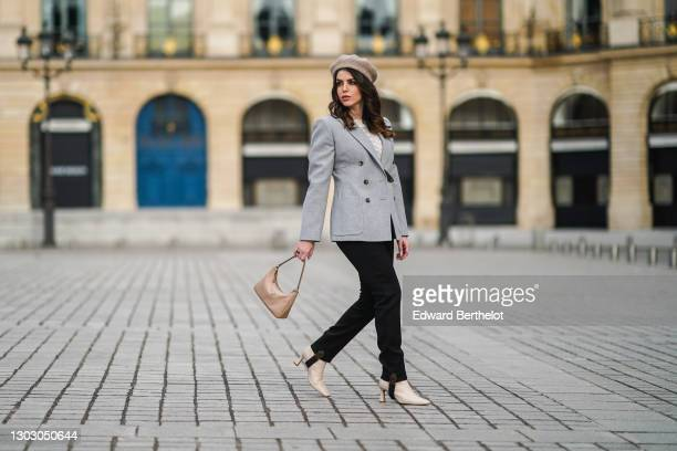 Sara Carnicella wears a beige wool beret hat from Zara, a gray blazer jacket from Louis Vuitton, a white pullover from Mango, black stirrup pants...
