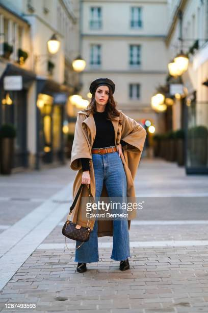 Sara Carnicella wears a beret hat from Anthony Peto, a beige oversized long coat with pagoda sleeves from Natan, a Vuitton brown monogram bag, a...