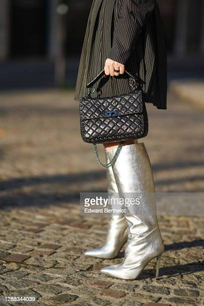 Sara Carnicella wears a black leather studded Rockstud Valentino bag, silver knee-high shiny pointy high heeled boots from Collini, on November 27,...