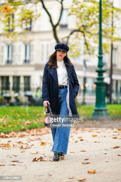 Sara Carnicella wears a blue beret hat a navy dark blue trench coat from Comptoir des Cottoniers a white shirt from Gaala a golden necklace from APM...