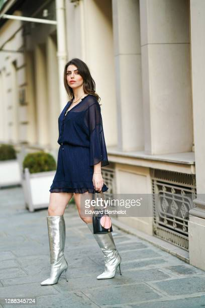 Sara Carnicella wears a blue flowing mesh dress with buttons from Hip+Happen, a Fendi black and pink leather bag, APM Monaco jewelry, Collini silver...