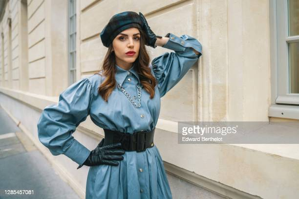 Sara Carnicella wears a blue Victoria Tomas dress with puff sleeves, black leather gloves from Celine, a large shiny leather belt from Elisabetta...