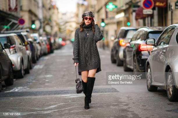 Sara Carnicella wears a dark gray knitted wool long pullover / dress with turtleneck from Parosh, a gray checked beret hat from Anthony Peto, red...