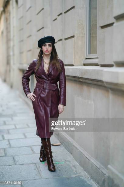 Sara Carnicella wears a golden necklace from APM Monaco, a black beret hat from Anthony Peto, a burgundy / purple leather dress with integrated large...