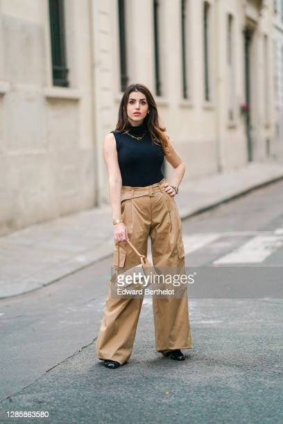 Sara Carnicella wears a golden necklace from APM Monaco, a black turtleneck sleeveless pullover / body from Wolford, beige pale brown flared pants...