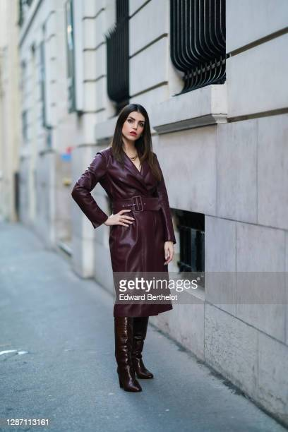 Sara Carnicella wears a golden necklace from APM Monaco, a burgundy / purple leather dress with integrated large belt from Natan, brown high leather...