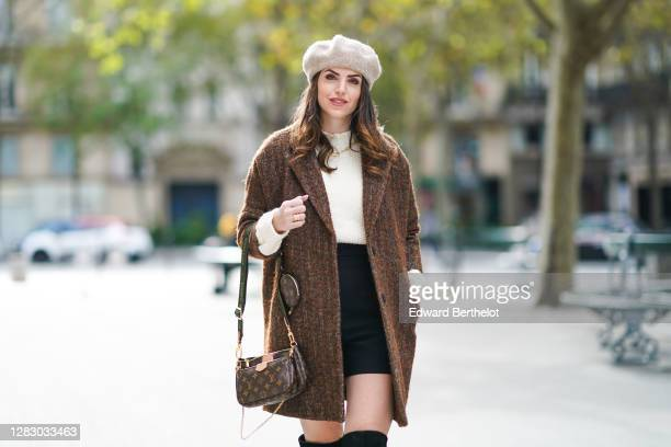 Sara Carnicella wears a gray wool beret hat from Zara, a brown oversized wool long coat from SeeUsoon, a white wool turtleneck pullover from Mango, a...